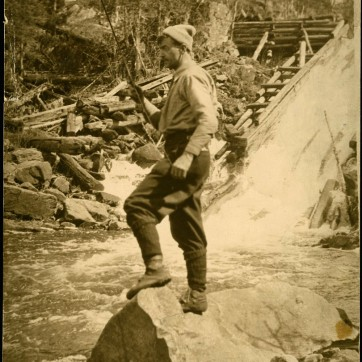 Tom Thomson, standing on a rock fishing in moving water. Photograph, LAC Box 03935